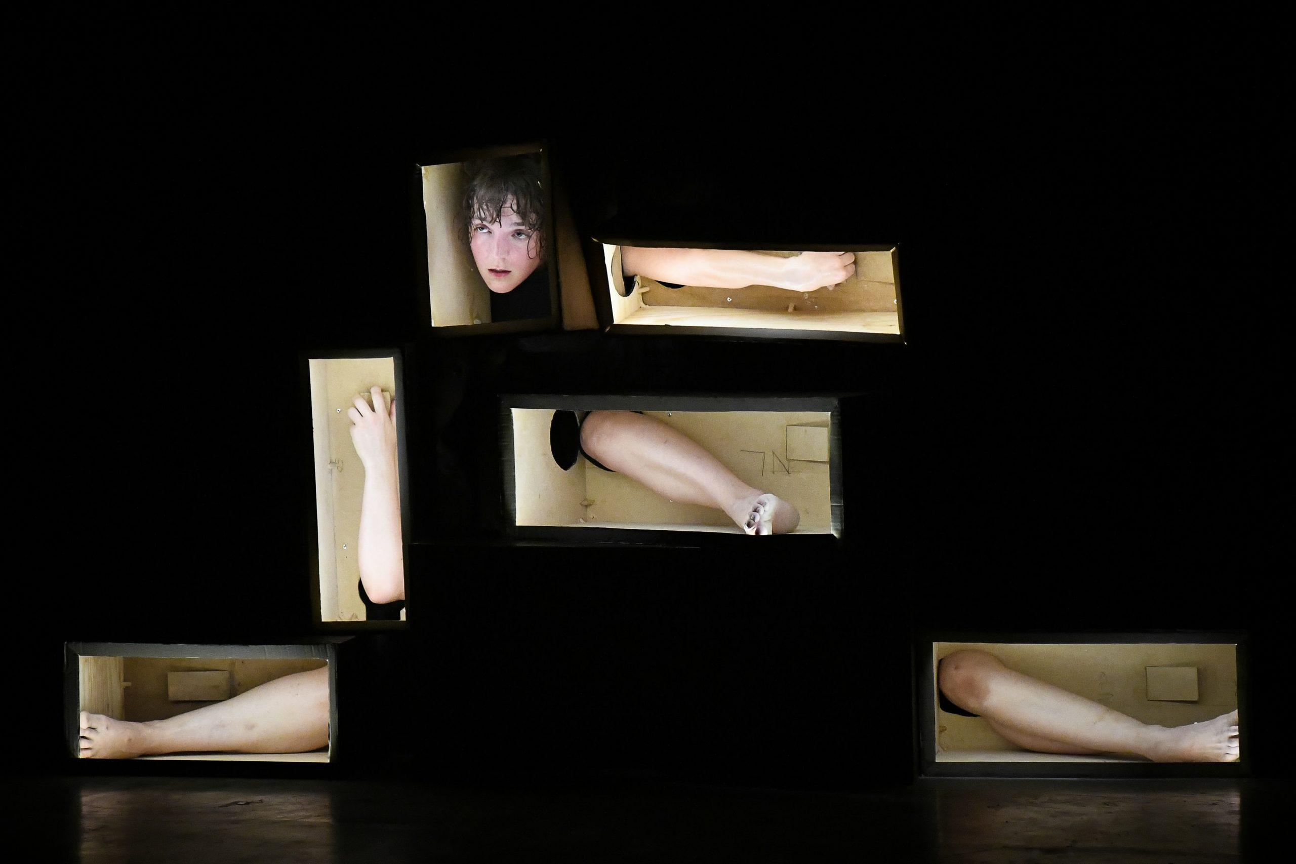 Ausschnitt der Performance, Körperteile in Boxen sichtbar wie im Zaubertrick